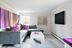 This basement media room has as much drama off the screen as on. Soft gray walls are punctuated by bold bursts of fuchsia and lilac in the pillows and artwork. A contemporary gray modular sofa with a chaise at one end offers a comfy spot to sprawl for TV viewing.