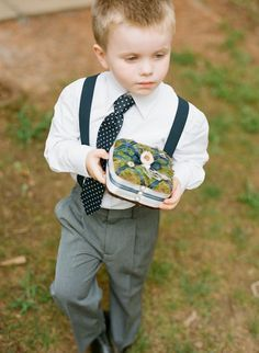 ring bearer in suspenders.. my favorite little boy look! he needs a bow tie though ;)