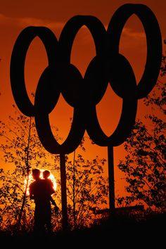Arte, luz, contraste y amor permiten captar una imagen como ésta. Un padre sosteniendo en brazos a su hijo y el mayor símbolo olímpico.  Foto: Getty Images