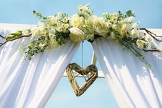 Artificial floral swag and hanging driftwood heart on the ceremony arch.