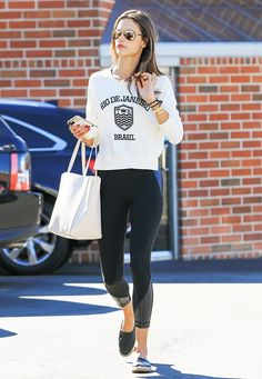Alessandra Ambrosio wears a graphic sweatshirt, leggings, espadrilles, and mirrored sunglasses