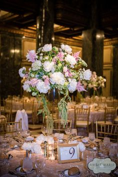A stunning arrangement of white peonies, miniature roses, Queen Anne's lace, and soft pink astilbes rest atop a tall cylinder vase. Votive candles, a crinkled rosy gold table cloth, gold chairs, and a gold photo frame displaying the table number accent the beautiful centerpiece. The wedding reception was held in the elegant Carnegie Music Hall Foyer. The John Parker Band, premier Pittsburgh wedding entertainers, provided the soundtrack for the evening. http://www.jpband.com/weddings/