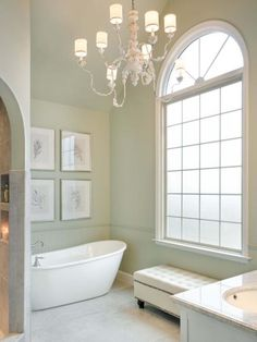 After a complete overhaul, elegant accents, like a grand iron chandelier, soaking tub and brushed-nickel hardware come together in this master bathroom.