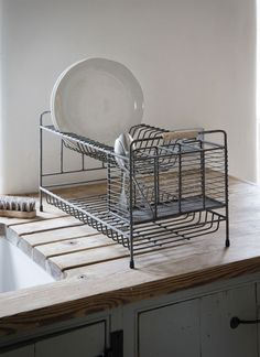 A stylish two-tier washing up drainer in distressed grey paint with a separate space for cutlery