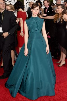 Felicity Jones is keeping her style streak going strong in this beautiful teal gown. The high neckline and darting make this number a standout on the red carpet. via StyleListCanada