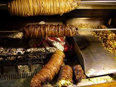 """Here is typical kokorec on the grill. When done, the sausage-like loaf is chopped and seasoned (to the right of the picture) for a sandwich or eaten without bread as a """"porsion""""."""