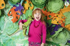 T-Rex telling secrets to a 5 year old redhead girl on a tropical jungle set at Emily Beatty Imagery's Dinosaur Mini Photo Shoots.