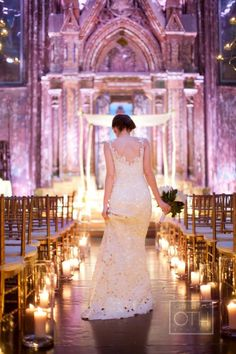 Gorgeous church venue with bride walking down the aisle lined by candles =)