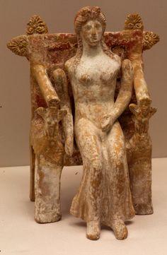 Terracotta_goddess_4th_century_BC_Staatliche_Antikensammlungen. Terrakottafigur einer Göttin auf einem Thron. DIe Arme waren beweglich angeordnet. Da die Puppe ursprünglich bekleidet war, sind die Gewandfalten nur angedeutet. Theben 4.Jhdt v:Chr