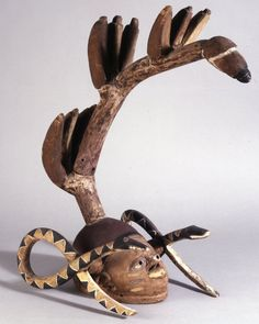 Gelede? mask (in form of head with snake either side and surmounted by bunches of plantains on stem) made of wood.