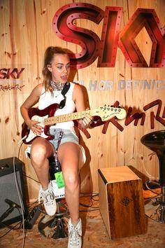 26/09 - Cara Delevingne tocando guitarra no estande da Sky no Rock in Rio 2015.