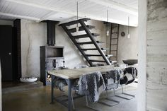 wood burning stove concrete table and grey stairs and exposed lightbulb pendants