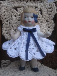 """A 31/2"""" Nippon all bisque pin jointed doll is my latest restored orphan. She is so tiny, so I named her Bitsy. Her lovely little crocheted dress came from Ebay, made by Jo Ann - fwangster. I added the navy ribbon. I love the tiny girls! She was a dirty mess, but cleaned up so nicely."""