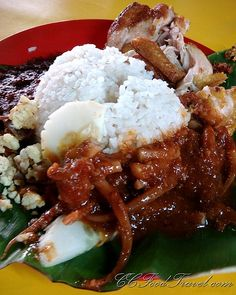 Nasi Lemak in Singapore/Malaysia | rice cooked in coconut milk, chili sambal anchovies, half a hard boiled egg, deep fried chicken, sambal squid, peanuts and cucumbers. Best wrapped or served on a banana leaf