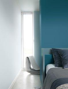 Deze slaapkamer herbergt een subtiel spel van kleuren en materialen. Het levendige 'fjord' combineert speels met het iets lichtere 'mineraal'. De stoel staat mooi in contrast met de fluwelen kussens. De wand links in 'kalmte' geeft een ontspannen gevoel door de weerkaatsing van het tegenlicht. Kleurgebruik: Fjord, Mineraal en Kalmte (collectie: Eenvoud Siert).