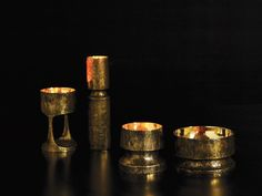 Crucible candleholders with deeply textured exterior and smooth reflective interiors