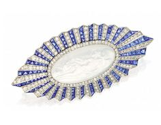 AND DIAMOND BROOCH, PAUL BRANDT, CIRCA 1920.  The oval moonstone cameo depicting a reclining maiden attended by a cherub, the navette-shaped frame decorated with alternating bands of calibré-cut sapphires and single-cut diamonds, the total diamond weight approximately 4.75 carats, mounted in platinum, cameo signed P. Brandt.