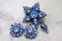 Vintage Judy Lee Blue Rhinestone Flower Brooch Pin Earrings Demi is designed with shades of sapphire and baby blues with a variety of chatons: pear, baguette, navette, and round.  This set is stunning