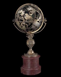 The fretted gilt-brass celestial globe on its marble and brass stand; French, mid-16th century.
