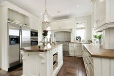 Simply spectacular white kitchen with matching timber bench tops and flooring.  Not to mention the 3 windows - Bonus.  White and Wonderful!