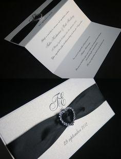 Inbjudningskort, bröllopsinbjudan tryckt på pärlemopapper. Brett svart sidenband och strasshjärta. Pappersboden