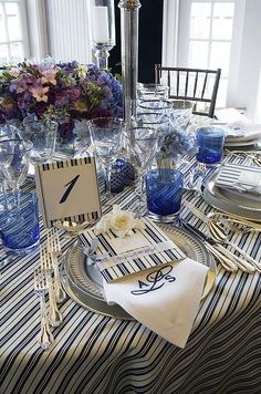 A navy blue and white striped table is set with a matching table number, menus and monogrammed napkins.