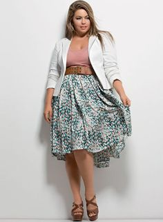 Fluvia Lacerda in teal/greyscale patterned shift skirt, broad beige belt, blush blouse, mocha plats, eggshell blazer, blush lipstick