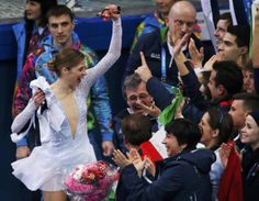 """Carolina Kostner of Italy is greeted by her teammates in the """"kiss and cry"""" area during the Team Ladies Short Program at the Sochi 2014 Wint..."""