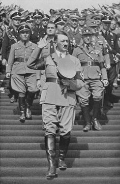 With his hand raised in a salute, Chancellor Adolf Hitler walks down the steps to the Zeppelinfeld during Reichsparteitag (Reich Party Day) ceremonies in Nuremberg. Behind him stands Robert Ley (left), Rudolf Hess (centre), and Heinrich Himmler (behind Hess). (September 10-16, 1935)