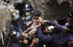 Rescue workers carry a child who was rescued from the rubble at the site of a collapsed residential building in Mumbai, India, in September.  Reuters