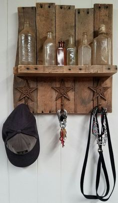 Custom display piece made from reclaimed pallet wood. Features one rustic shelf and three metal star hooks for hanging coats/keys/jewelry, etc. Finished with a matte poly finish to bring out the grain
