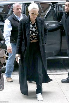 More of a cover up: The model and actress covered up a little more in a black trench coat over a black and white crop top as she ran errands in New York on Wednesday