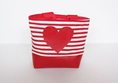 Let your little girl feel like a grown-up with this adorable handmade purse designed to fit all her special treasures. It's made out of red vinyl,