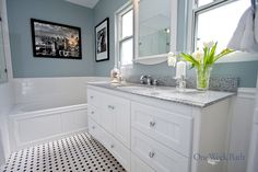 One Week Bath's take on a traditional black and white bathroom remodel with a single undermount sink vanity with a whole bunch of storage space This traditional design bathroom remodel features a black and white checkered floor and colorful blue walls to add a bit of personality. This style of bathroom remodel is a great idea for someone with traditional tastes, but who wants a pop of color. #OneWeekBath #Bathroom #Remodel