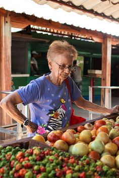 Residents in Cuba like Yolanda Horruitiner, above, shopping at a pricey farmers' cooperative market, struggle to find ingredients to stock their kitchens. (Photo: Lisette Poole for The New York Times)