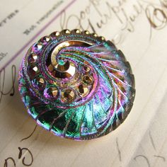 Peacock feather Czech glass button - 27mm - aqua, fuchsia, emerald green, orange, hand painted gold. $5.50, via Etsy.