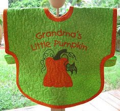 Quilted Toddler Bib pattern from www.QuiltyIndulgence.com      The free machine embroidery design is from the website,  www.sewswell.com   This is a winner for sure!