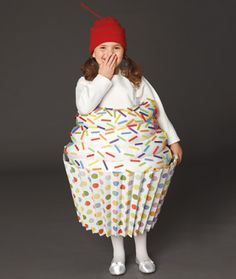 Cupcake costume using a round laundry basket covered in accordion-folded wrapping paper for the base and 2 pairs of adults sized tights stuffed with batting for the frosting (sprinkles are cut up multi-colored straws) with a red cap & pipe cleaner (for cherry on top!) and suspenders to hold it all up.