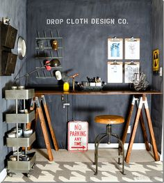 Work space featuring DIY sawhorse desk, chalkboard wall, industrial accents