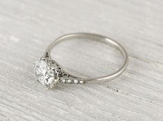 Elegant vintage engagement ring made in platinum and centered with an approximate one carat EGL certified cushion cut diamond with G-H color and VS1 clarity. The band is fine and dainty and has a comfortable light feel on the finger. Circa 1920