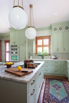 The details in this kitchen are what truly brings the space together. The homeowners wanted a unique renovation, but were concerned with maintaining the home's integrity, so designers combined a few unique, more modern touches with traditional features to create this stunning kitchen. Wallpaper is used throughout the space to add color and warmth while maintaining the traditional feel of the home