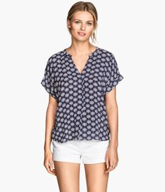 Wide-cut blouse in crinkled woven fabric with a V-neck and pleat at front. Short sleeves with sewn cuffs. Gently rounded hem.