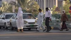 Abu Dhabi (Emirate), Crossing (Action of Crossing), Cycling (Procedure), Bicycle, City Traffic, Pedestrian, Shadow, Car, Street, Walking, Large City, Sunshine, Day, Stock Footage,