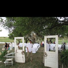 Old doors repurposed for outdoor chapel entry - accented with burlap bows. Absolutely beautiful wedding.