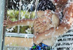 A mother holds onto her baby as they cool off in a fountain as temperatures rallied to 99.68 degrees Fahrenheit (37.6 degrees Celsius) in Taipei, Taiwan, on July 9, 2012.