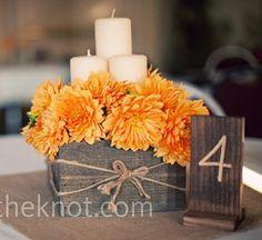 Schöne Idee auch in einer rustikalen Holzkiste mit Kerzen! Blumen dann natürlich eine Mischung an Gerbera. Tischnummer/Tafel kann entweder ins Gesteck oder extra wie oben abgebildet platziert werden /alternativ auch Wiesn-Herz mit der Tischnummer neben dem Gesteck platzieren!