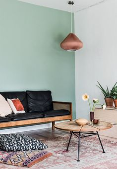 Living room in green and pink shades with a leather couch.