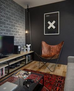 The design utilizes a mixture of a warm industrial trend with vintage, upcycled pieces. For instance, the caged bulb next to the warm leather sling chair is made from a vintage barn pulley and the headboard in the bedroom is a repurposed vintage door.
