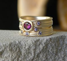yellow gold nest style ring with grape garnet and tanzanites