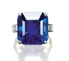 AN EXCEPTIONAL SAPPHIRE RING, BY CARTIER Set with an octagonal-cut sapphire weighing 21.29 carats to the baguette-cut diamond shoulders and platinum hoop, size 2½ Mounted by Cartier, no. indistinct